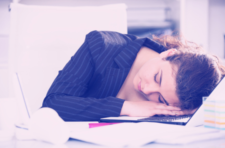 expertize: Woman worker is sleeping after productive day at work in office.