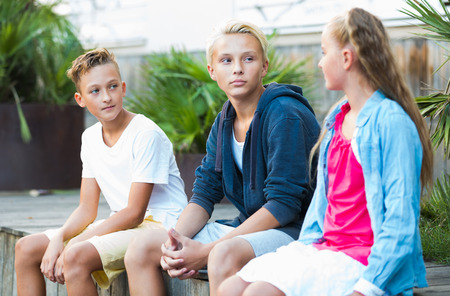 Group of positive children relaxing and chatting in town square garden