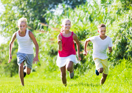 Three smiling adult kids playing active games in summer park chasing each other Stock Photo