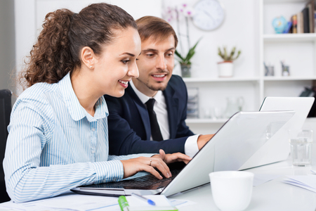 Glad happy  efficient business female assistant wearing formalwear using laptop in company office