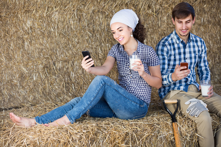portrait of two young happy farmers taking a pause in the hay and having their phones in hands