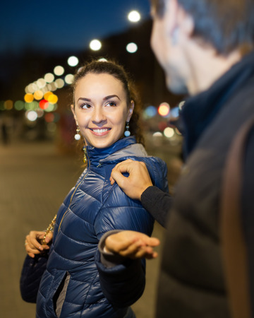 sidewalk talk: Young brunette girl and hadsome man meeting at night street