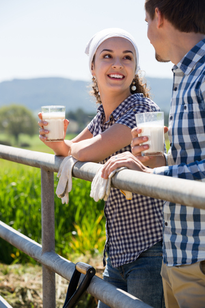 Portrait of happy man and woman taking a pause and holding glass with milk Stock Photo