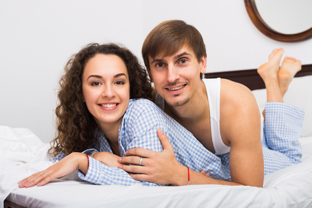 Young adults posing in family bed and smiling