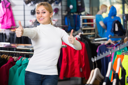 25 35: Portrait of a cheerful smiling young blonde woman in the clothing store