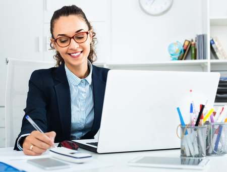 Cheerful positive business lady sitting at office desk with laptop