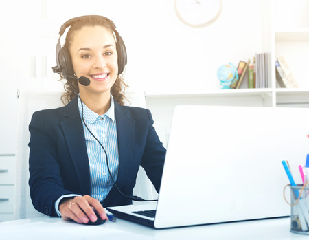 Cheerful girl with headset and laptop answering call in office