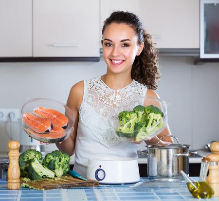 jorobado: Retrato de joven preparando pescado y verduras en el vapor Foto de archivo
