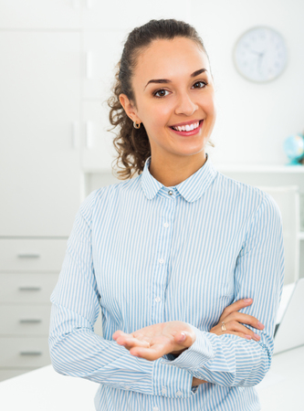 portrait of friendly smiling young business lady standing near office desk Stock Photo