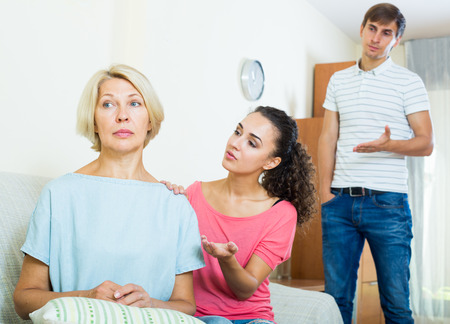 Frustrated woman watching how adults trying to reconcile with her Stock Photo