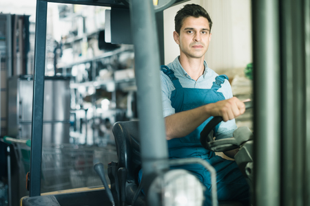 concentrated man in unifom is using ?argo moving machine in the warehouse building store Stock Photo