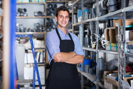 Portrait of professional working male in uniform on his workplace in building store.