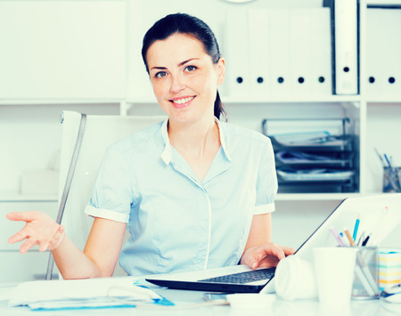 Portrait of young smiling female in the office sitting at the table