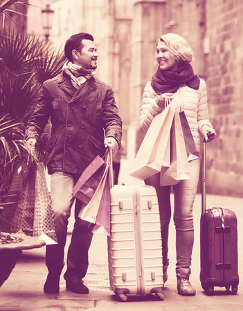 Mature travellers walking in European town and carrying shopping bags Stock Photo