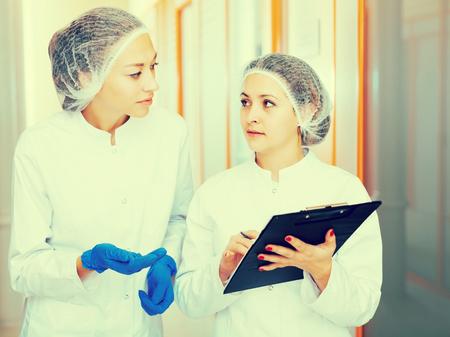 Freundliche junge Ärzte beschreiben Schönheitsprozeduren im ästhetischen Medizinzentrum Standard-Bild - 84969156