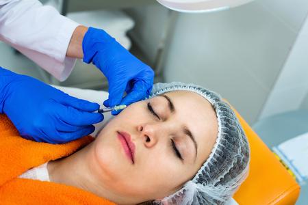 Doctor de la mujer que hace la inyección de la belleza al cliente alegre joven alegre de la hembra