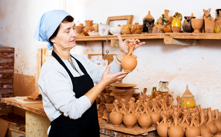 Glad elderly female master among the finished products in the pottery workshop