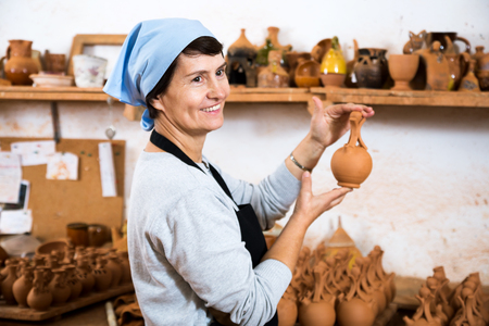 Smiling senior female master among the finished products in the pottery workshop