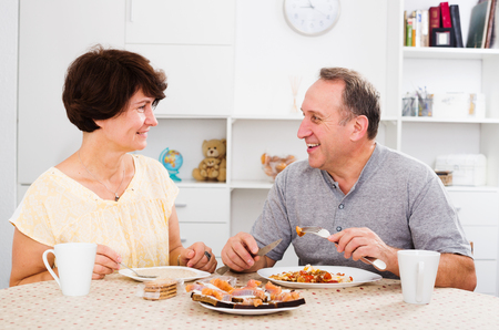 cheerful senior couple having lunch together at home