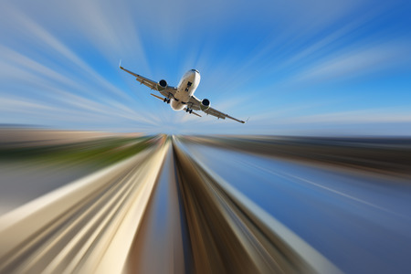 quickness: Airplane in motion over roadway on blur blue sky background