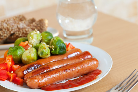 Three grilled sausages with vegetables on  plate