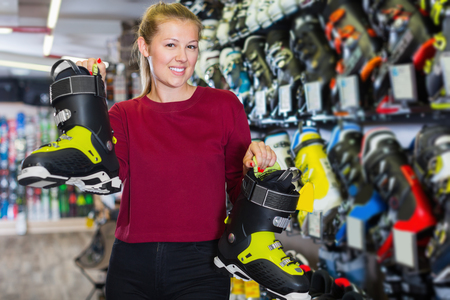 Smiling woman is choosing stylish boots for skiing in sport shop