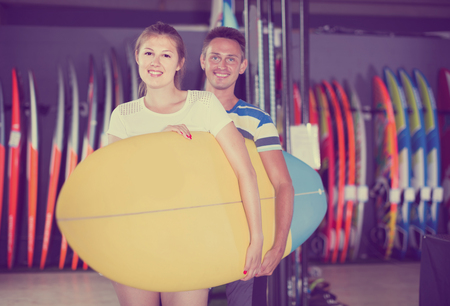 Young italian couple is posing in surfboard store on the beach. Stock Photo