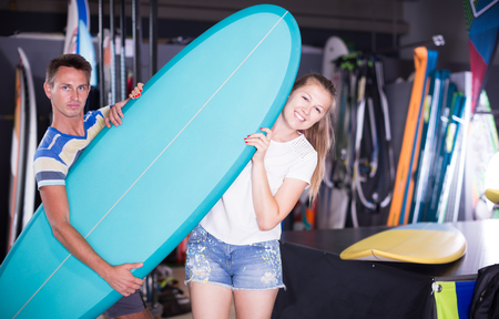 Portrait of adult guy with girl who are buying surfboard in store in time summer holidays