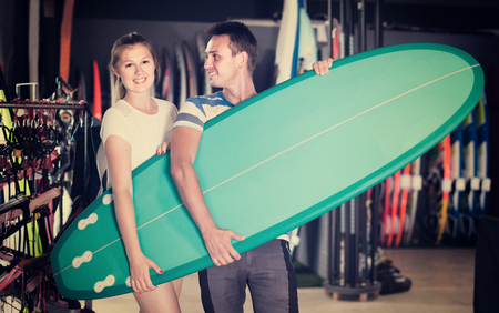 Young swedish couple is posing in surfboard store on the beach. Stock Photo