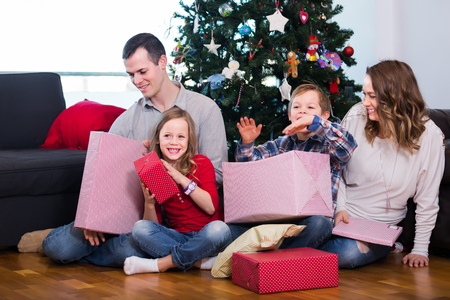 familia animada: Large happy family handing gifts to each other during Christmas at home