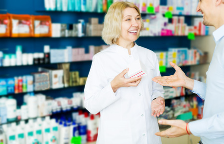 Portrait happy helpful pharmacist serving and consulting man in pharmacy Stock Photo