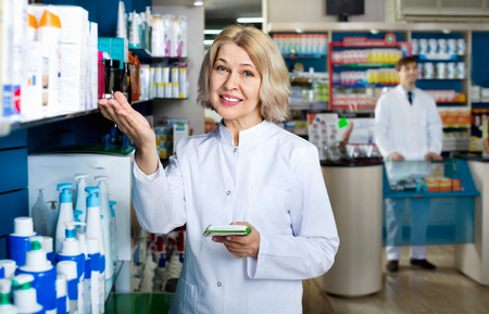 Portrait of two friendly glad smiling pharmacists working in modern farmacy Stock Photo