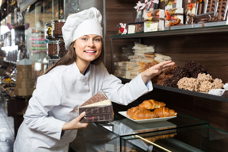 Young shopgirl posing with  chocolate and confectionery at display