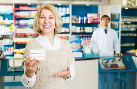 Mature smiling woman near counter in pharmacy drugstore