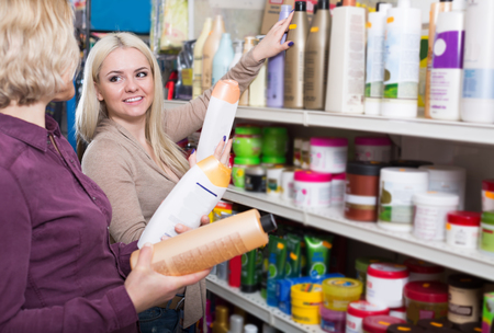 mother and adult daughter in good spirits selecting shampoo in the store  together