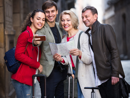 Smiling family of four with trunks taking selfie on camera in smartphone in the city street. Selective focus Stock Photo