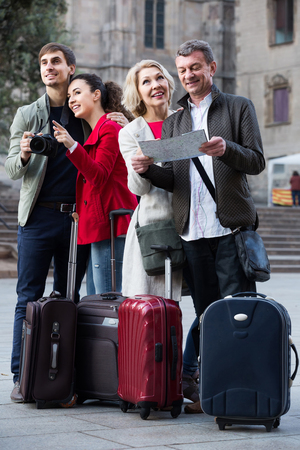 Portrait of positive spanish tourists with map and baggage seeing the sights in European city Фото со стока