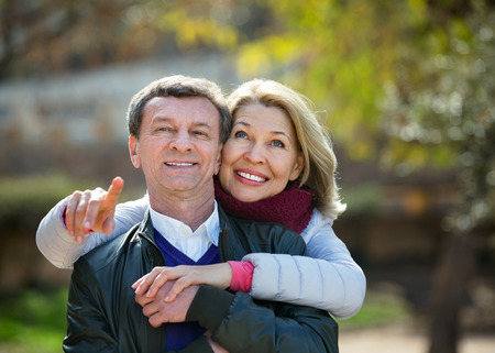 Portrait of happy charming positive elderly couple in sunny spring day
