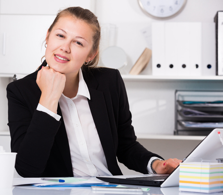 expertize: Female employee is posing while working behind laptop in the office. Stock Photo