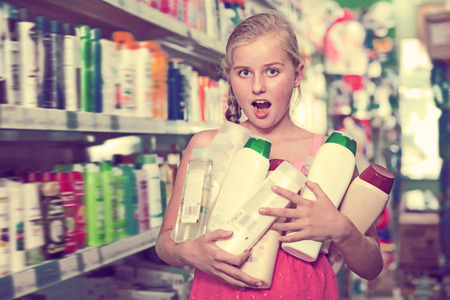 Happy girl holding shampoo and shower gel at the supermarket