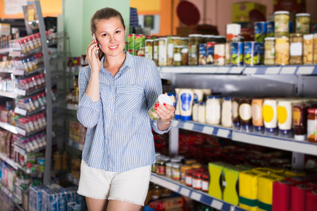 25 35: Woman 25-35 years old is talking phone and choosing mushrooms in shop.