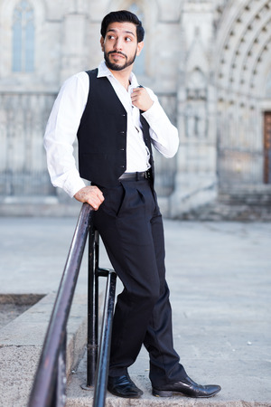 Confident young man posing near iron banisters outdoors