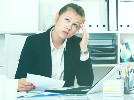 expertize: Young female in black suit is having complicated issue with project in office. Stock Photo