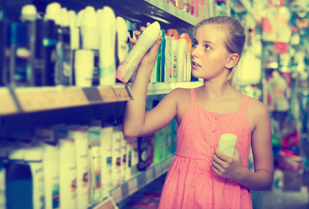 Young girl holding body spray in the hand at the shop