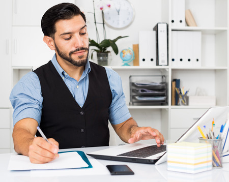 expertize: Young male is reading documents and looking in laptop in office. Stock Photo
