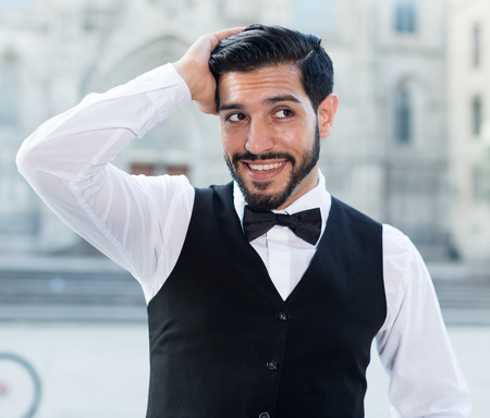 Handsome young man in formalwear adjusting his hairstyle and smiling standing outdoors Stock Photo