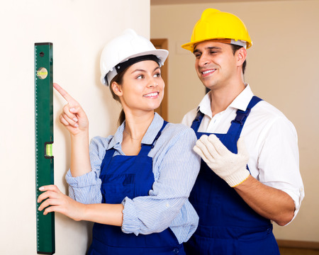 Positive female constructor showing assistant measuring the wall indoors. Focus on the woman