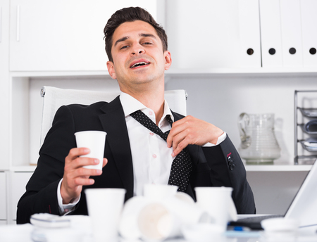 Relaxed businessman giving thumbs as sign of successful finish of work Stock Photo
