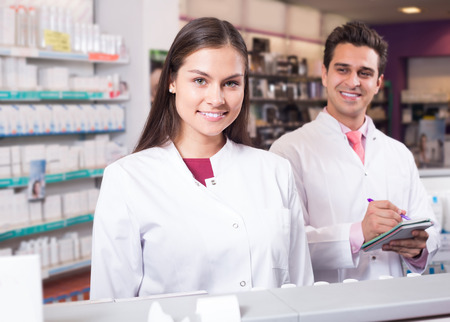 Professional smiling american pharmaceutists at reception of drugstore ready to help