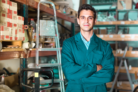 Portrait of young working male in uniform on his workplace in building store.